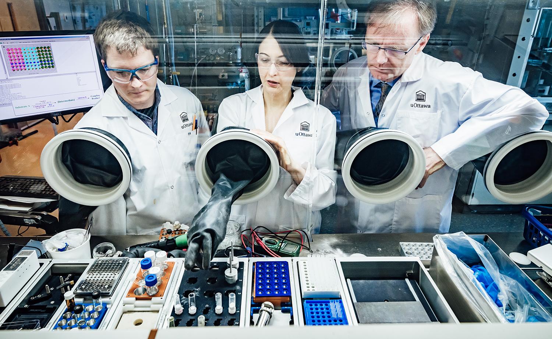 Le professeur Michael Organ et deux autres scientifiques travaillent dans un laboratoire et portent un sarrau à l'effigie de l'Université d'Ottawa.