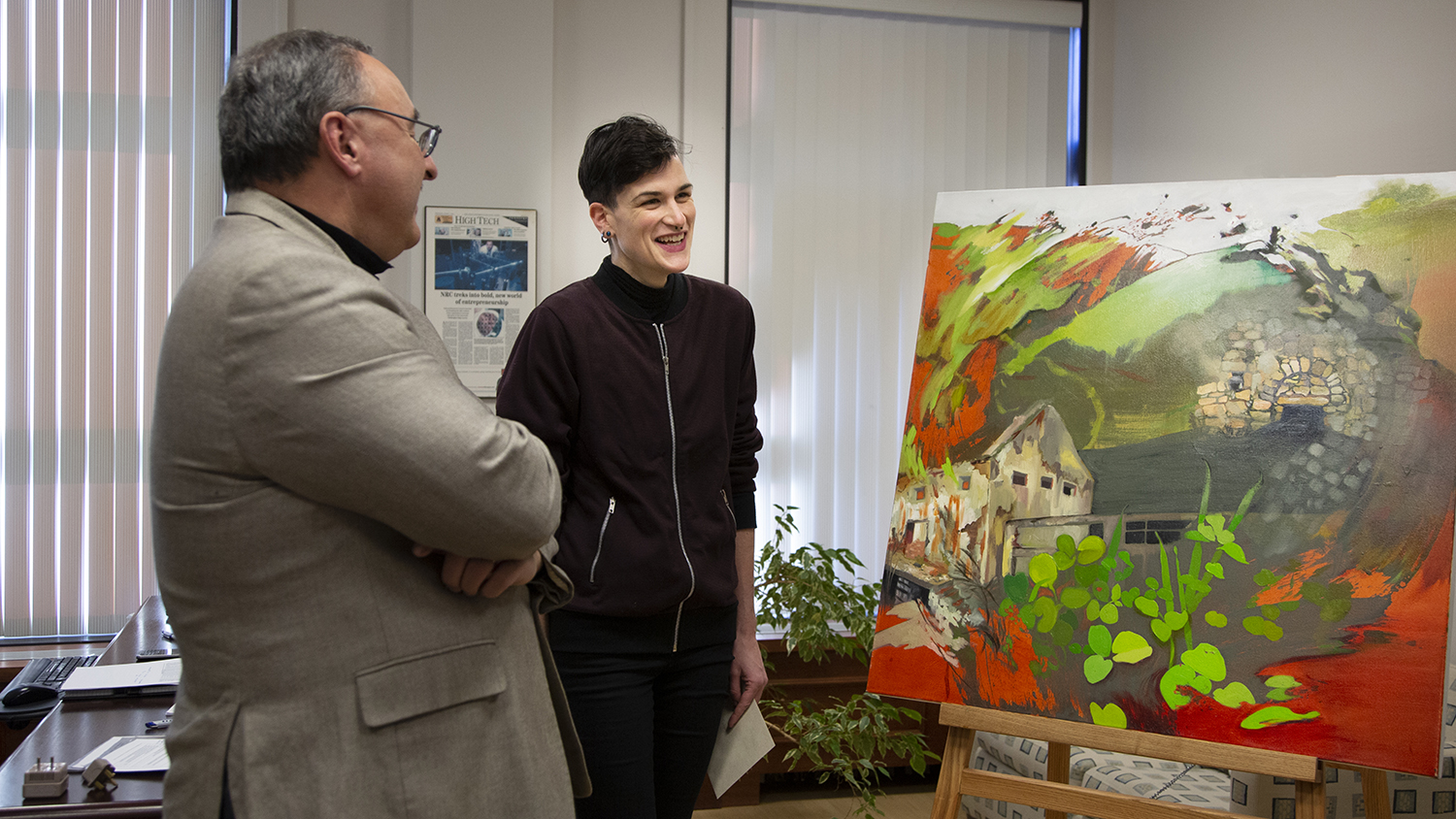 Sylvain Charbonneau and Nic Cooper are standing and smiling in front of Cooper's painting.