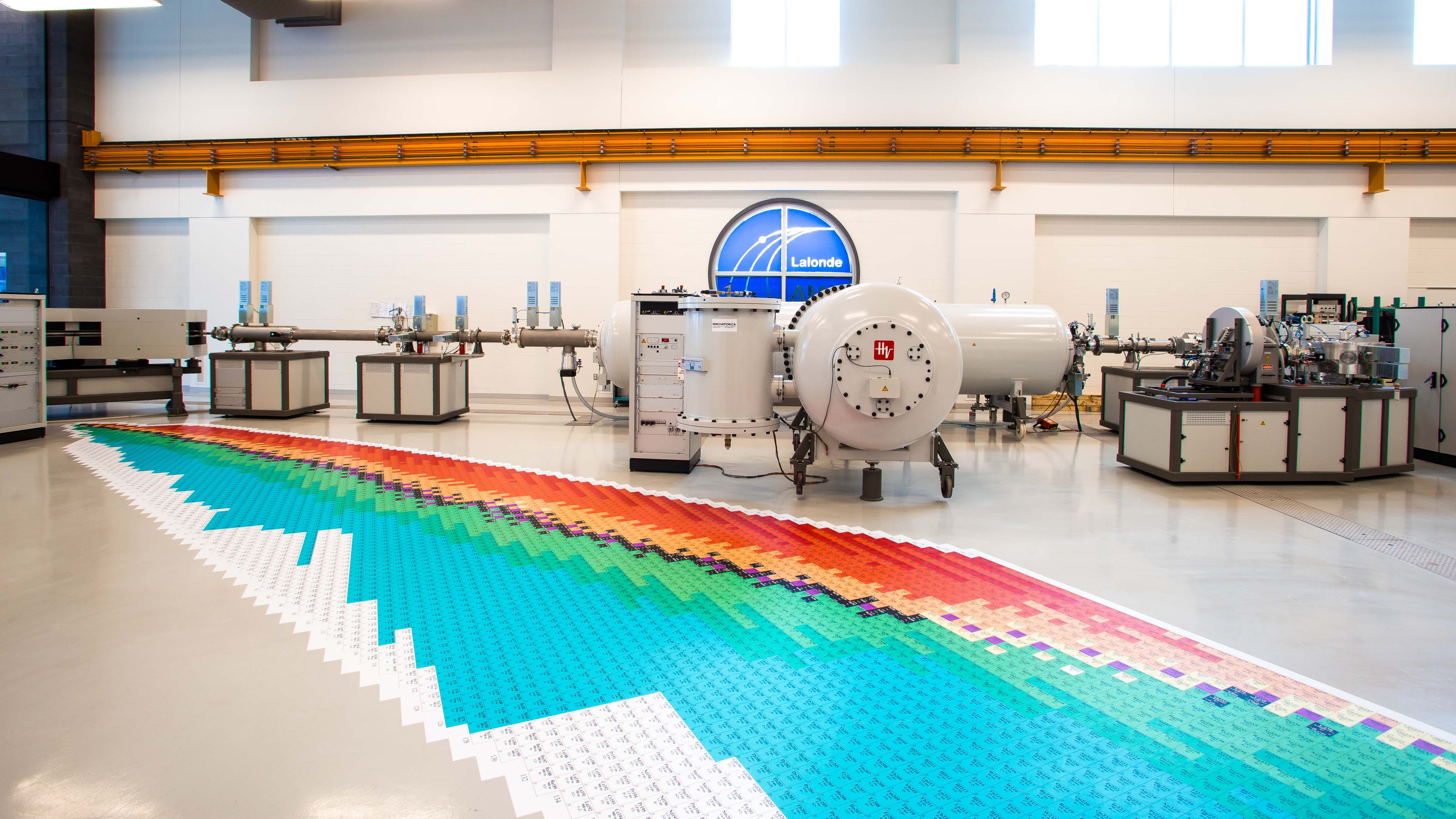 Interior of a laboratory showing an accelerator mass spectrometer and a gigantic periodic table printed on the ground