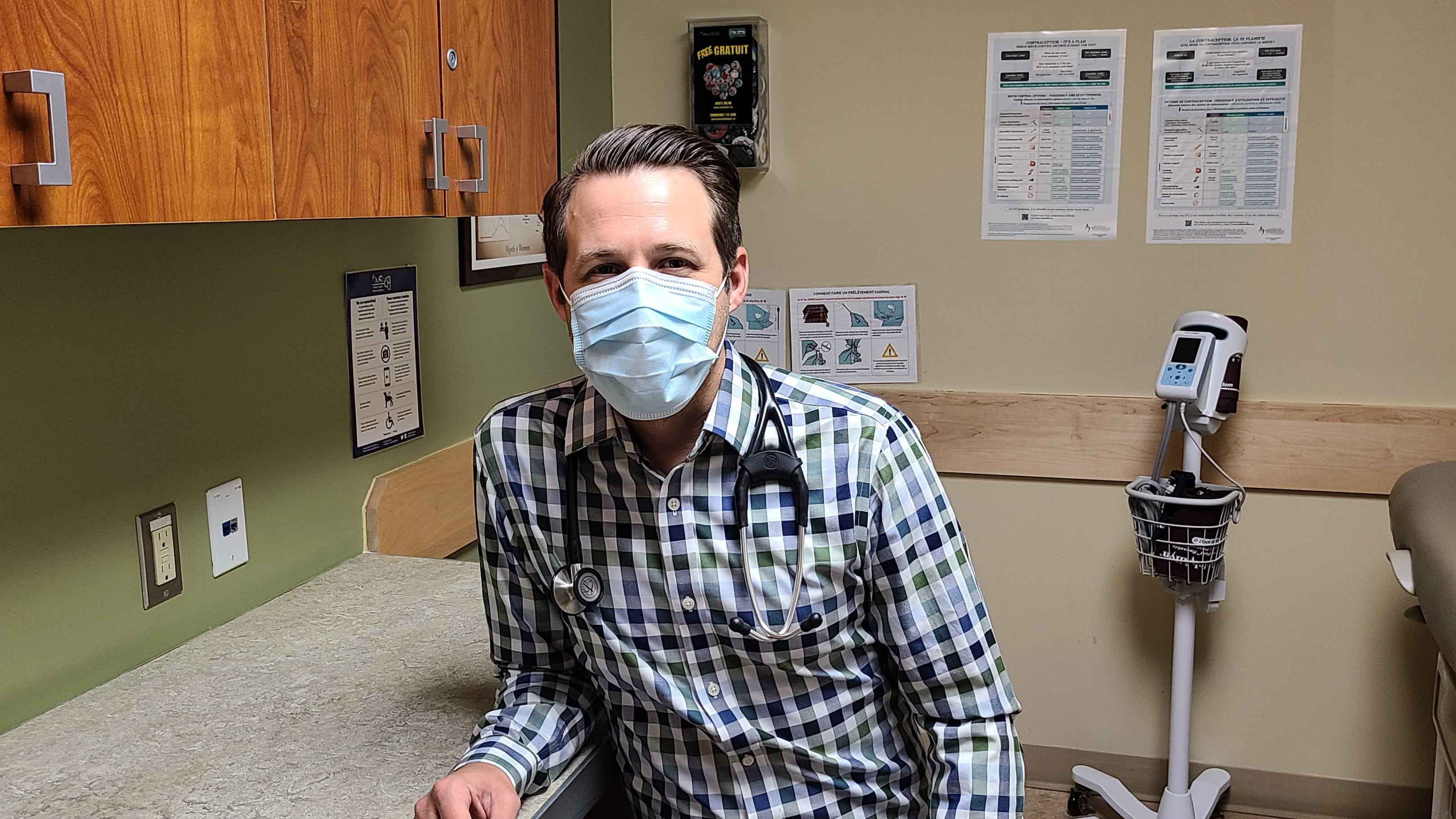 A nurse wearing a mask is sitting in a clinic.