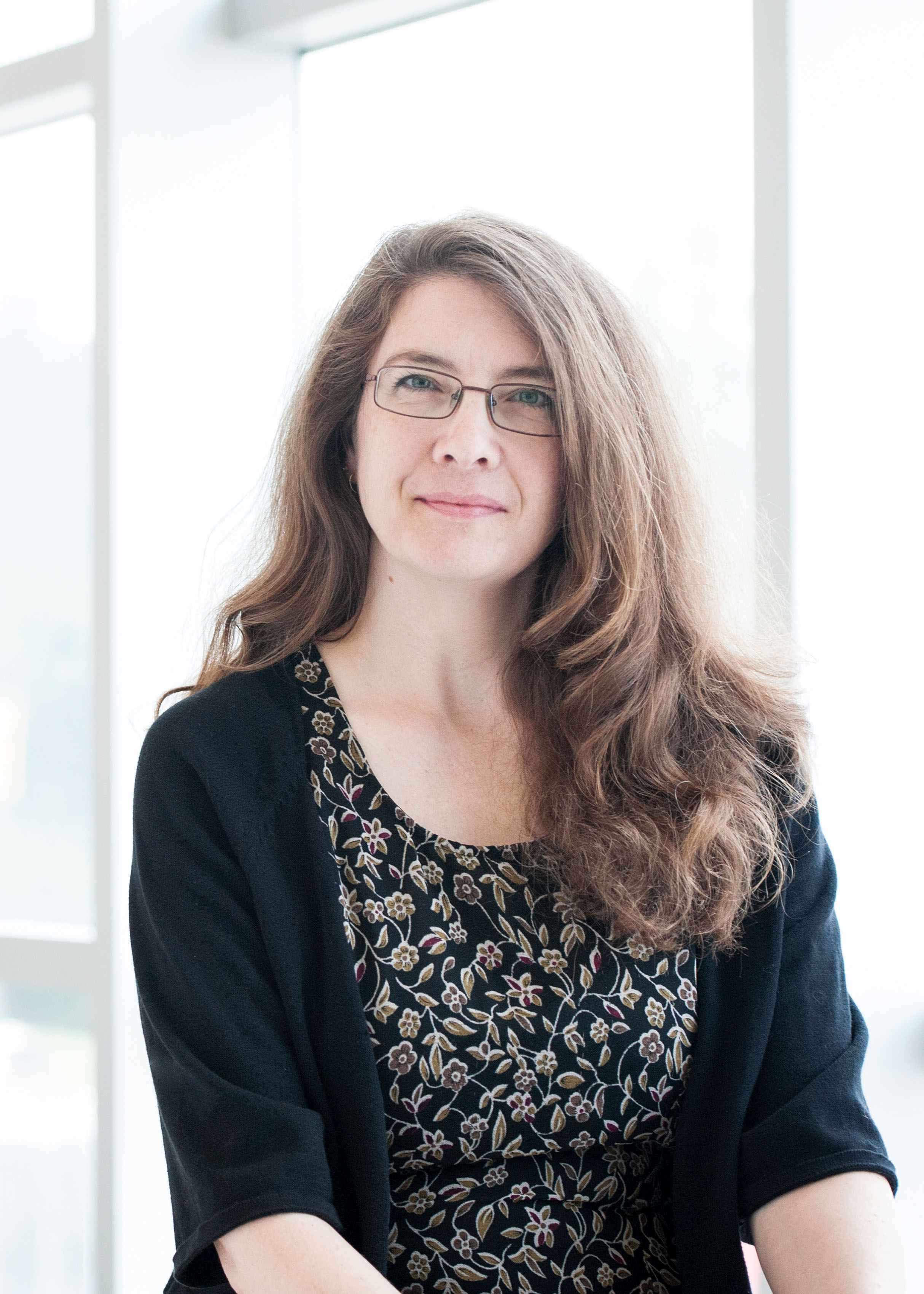 Head shot of Professor Ivy Bourgeault standing in front of a window wall