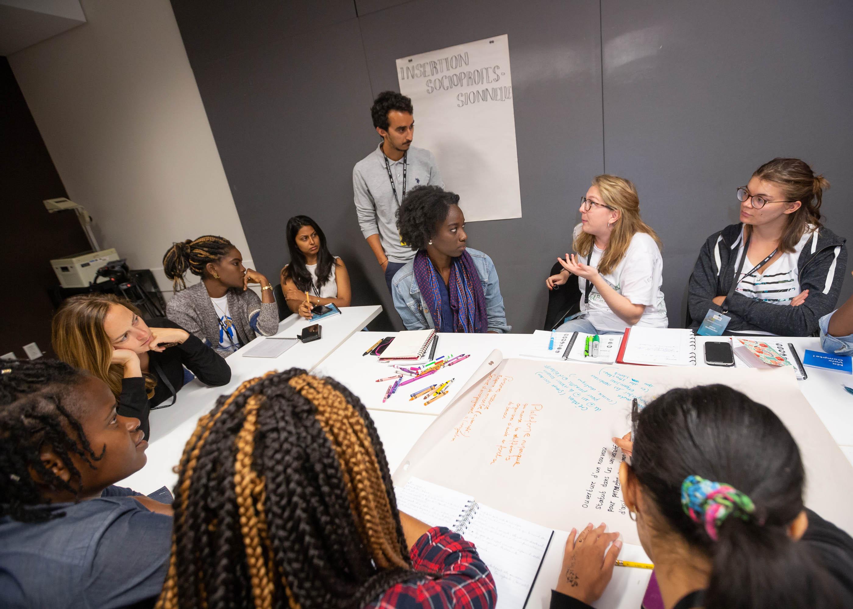 Un groupe d'étudiants travaillant et discutant ensemble dans un cercle.