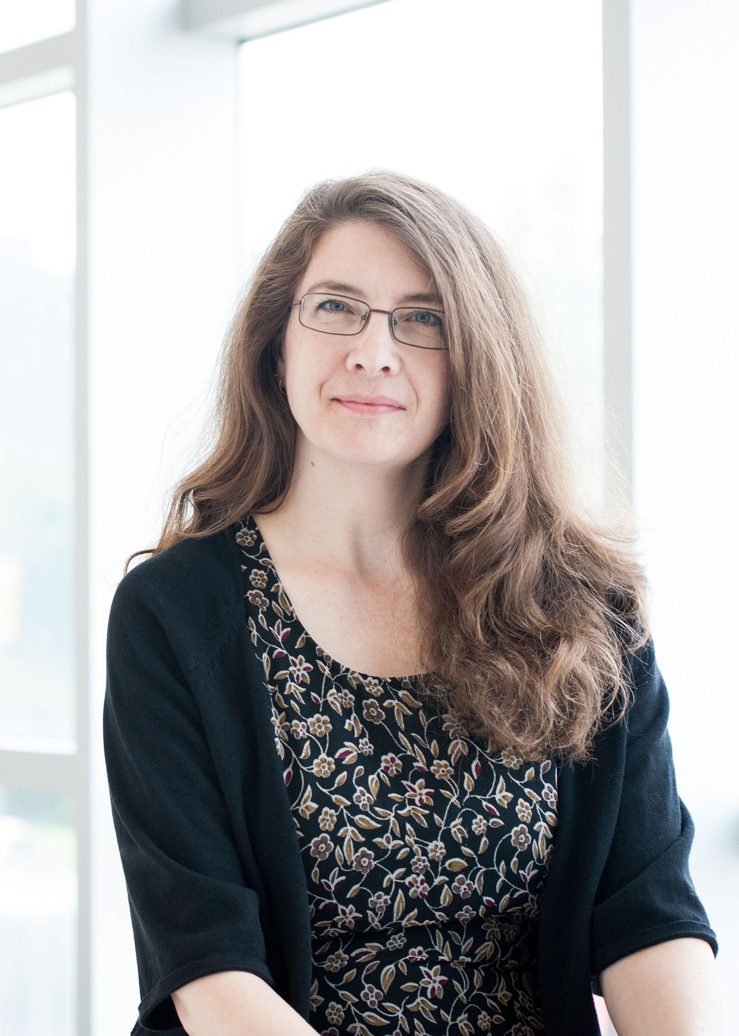 Portrait de la professeure Ivy Bourgeault debout devant un mur de vitre