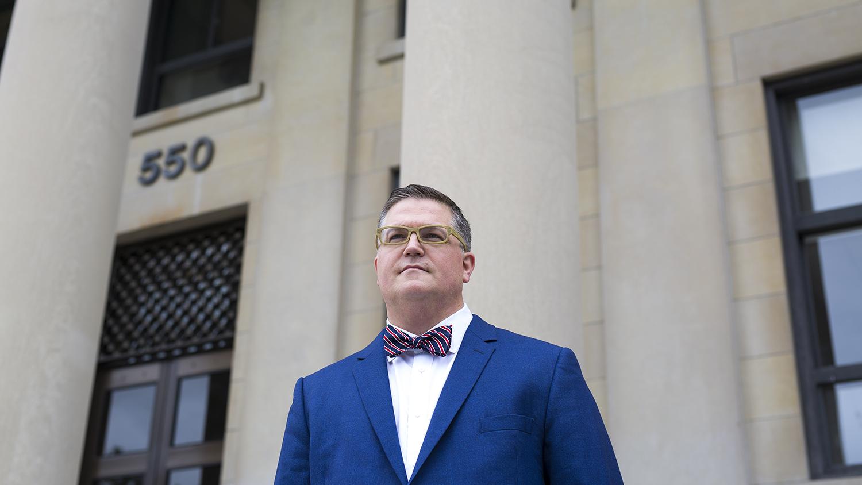Le professeur Larocque se tient debout devant le pavillon Tabaret