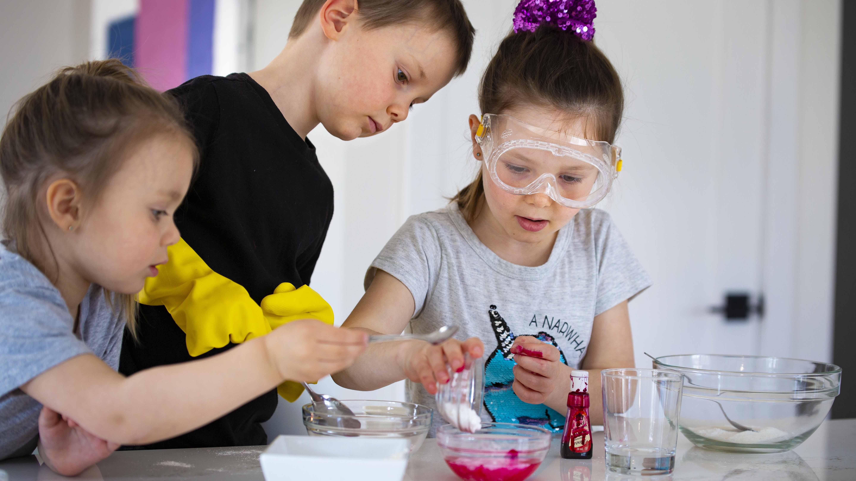Trois jeunes enfants font des expériences scientifiques