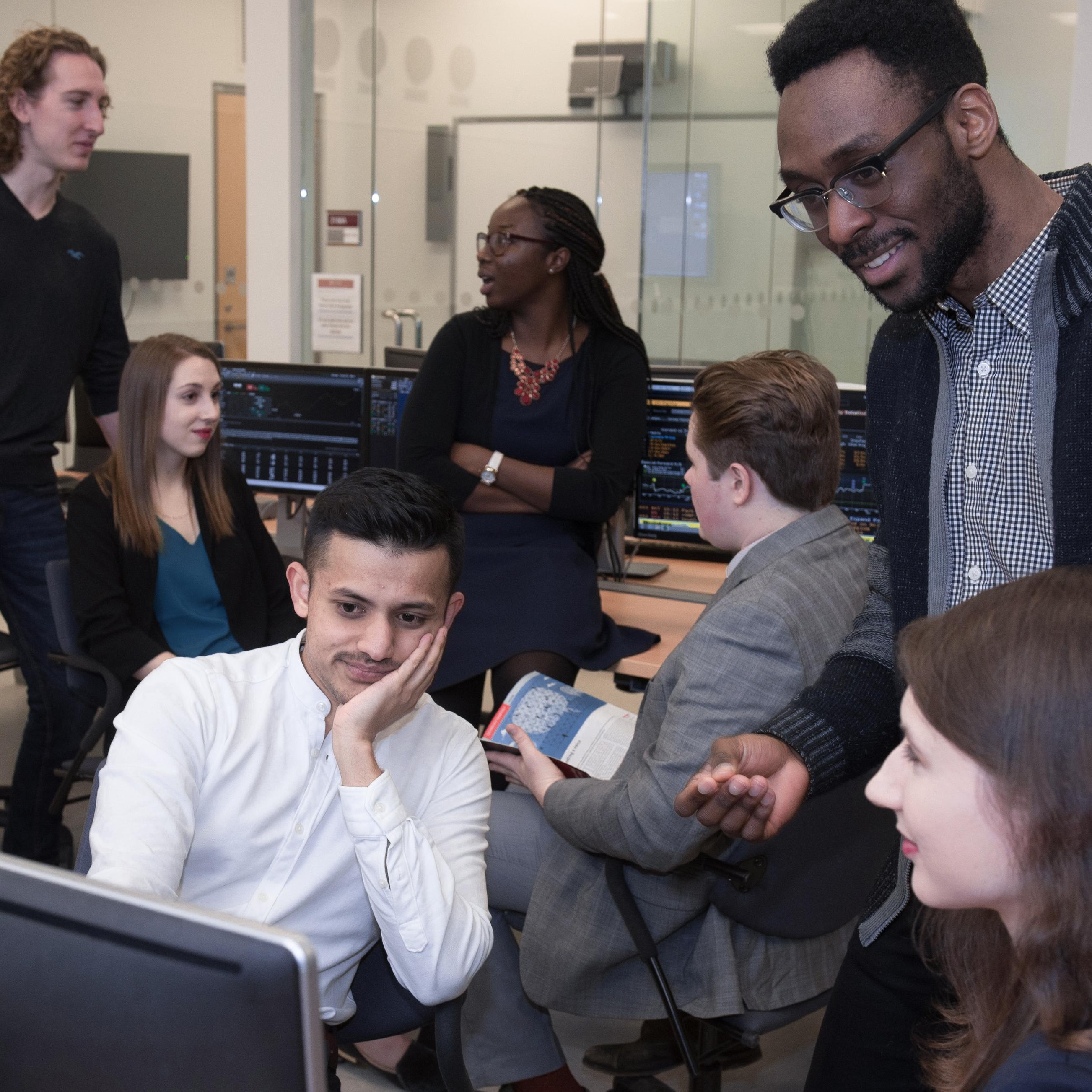Des étudiants qui discutent en regardant un écran d'ordinateur