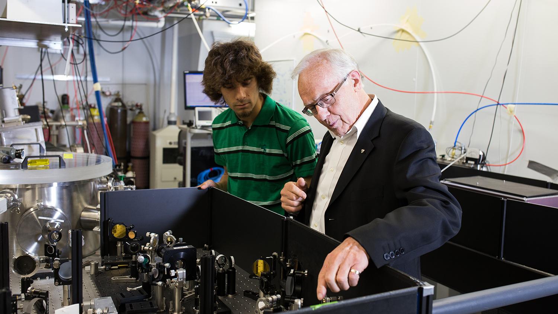 Paul Corkum montre des instruments optiques à un étudiant dans un laboratoire rempli de câbles.