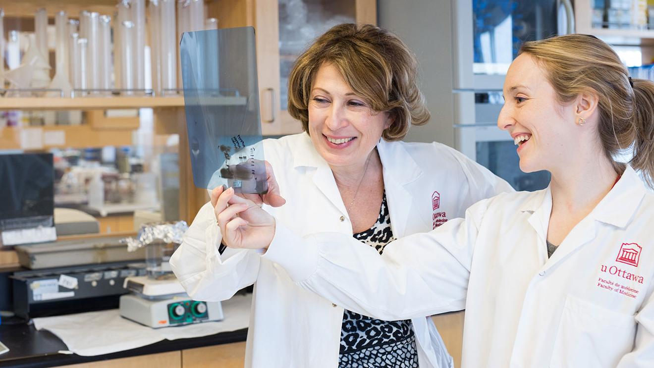 Mona Nemer dans un laboratoire de l'Université aux côtés de la doctorante Jamie Whitcomb.