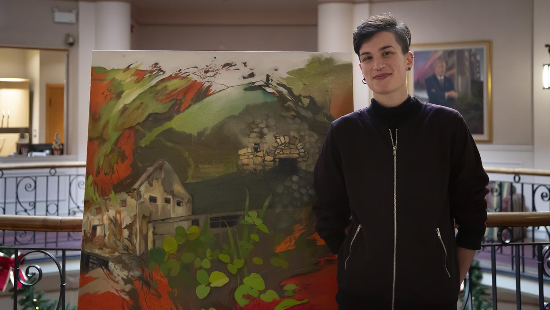Nic Cooper se tient debout à côté de sa toile