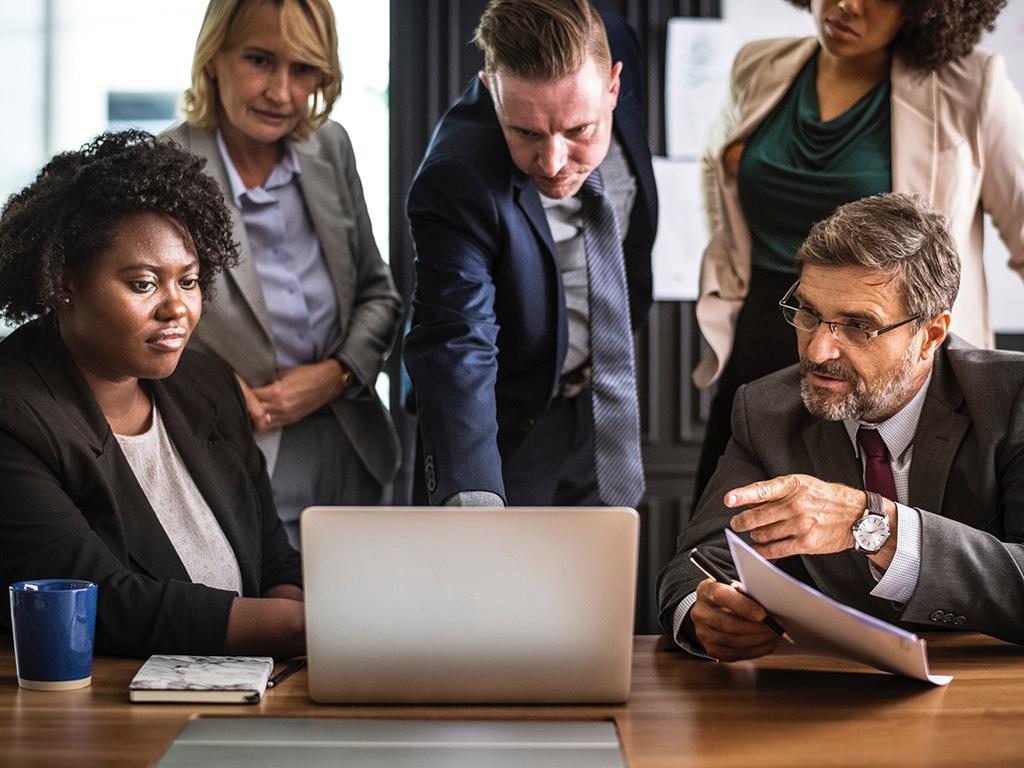un groupe de personnes qui discutent devant un ecran d'ordinateur