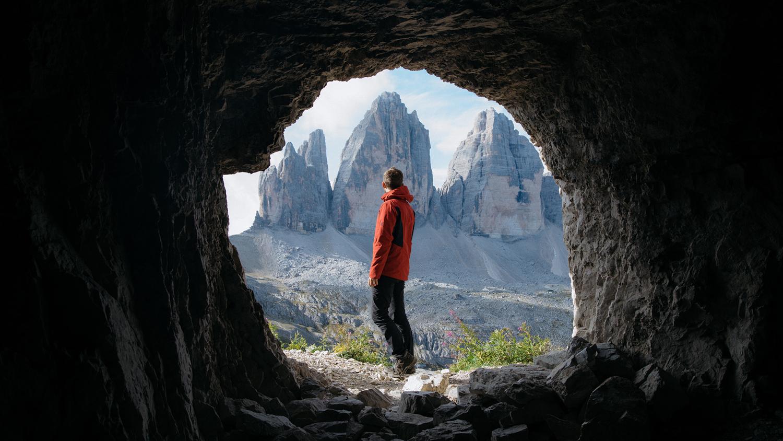 Un jeune homme vu de dos regarde l'horizon montagneux alors qu'il est au milieu d'une caverne.
