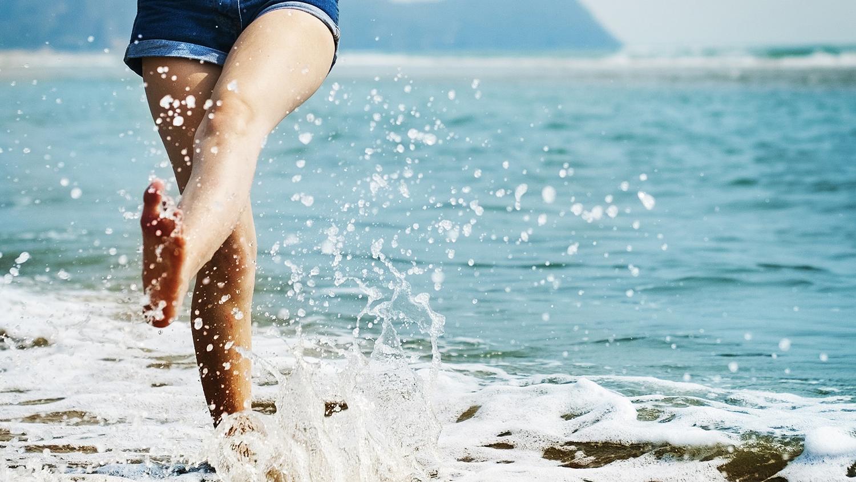 Les jambes d'une jeune femme éclaboussent l'eau sur la plage.