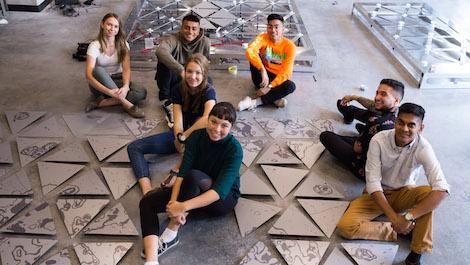 Etudiants assis par terre à l'intérieur du building STEM