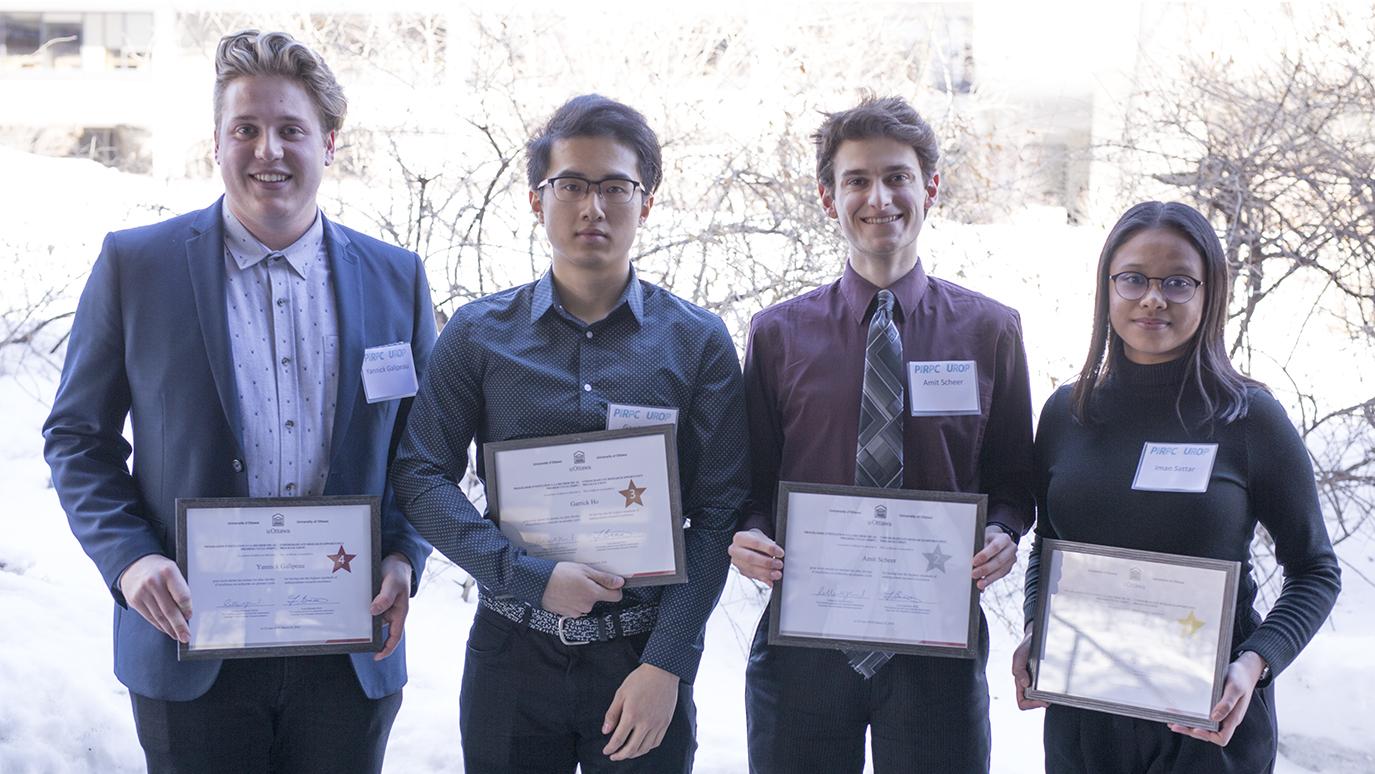 Quatre étudiants sont debout côte à côte et tiennent chacun un certificat dans leurs mains.