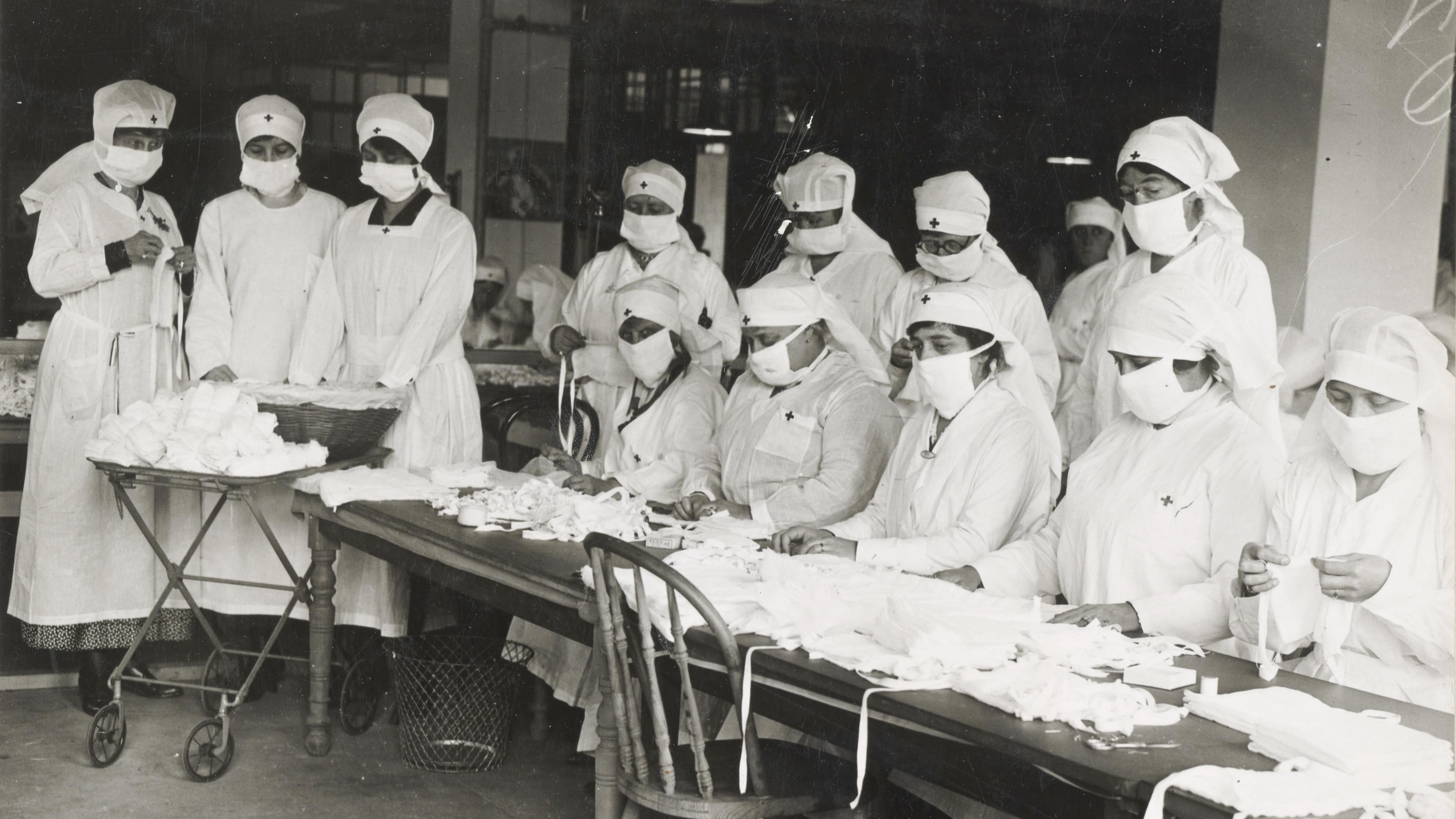 13 travailleuses de la Croix-Rouge produisent des masques contre la grippe.