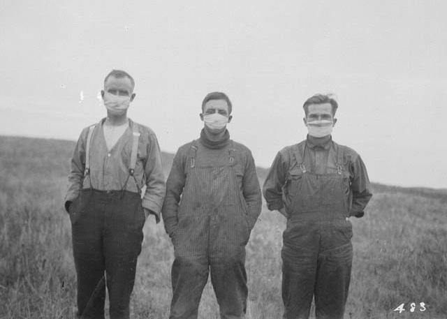 Trois hommes de 1918 portent un masque dans un champ.
