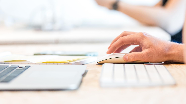 Une main sur une souris d'ordinateur est placée devant un clavier.