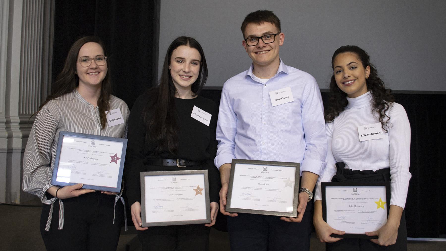 Quatre étudiants se tiennent debout avec un certificat entre les mains.