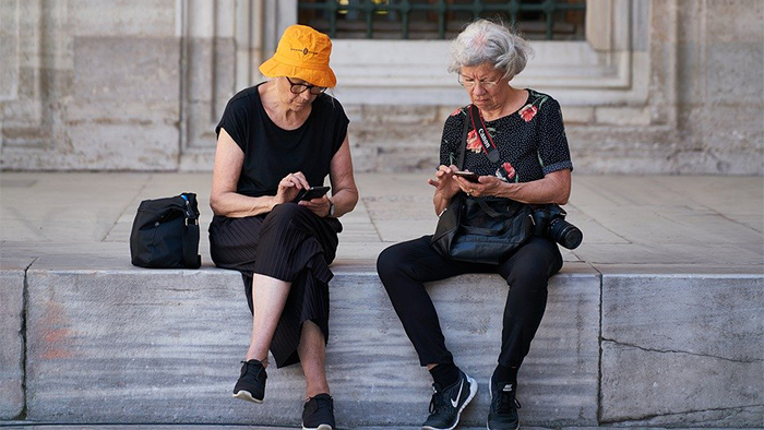 Two senior ladies sitting outside a monument