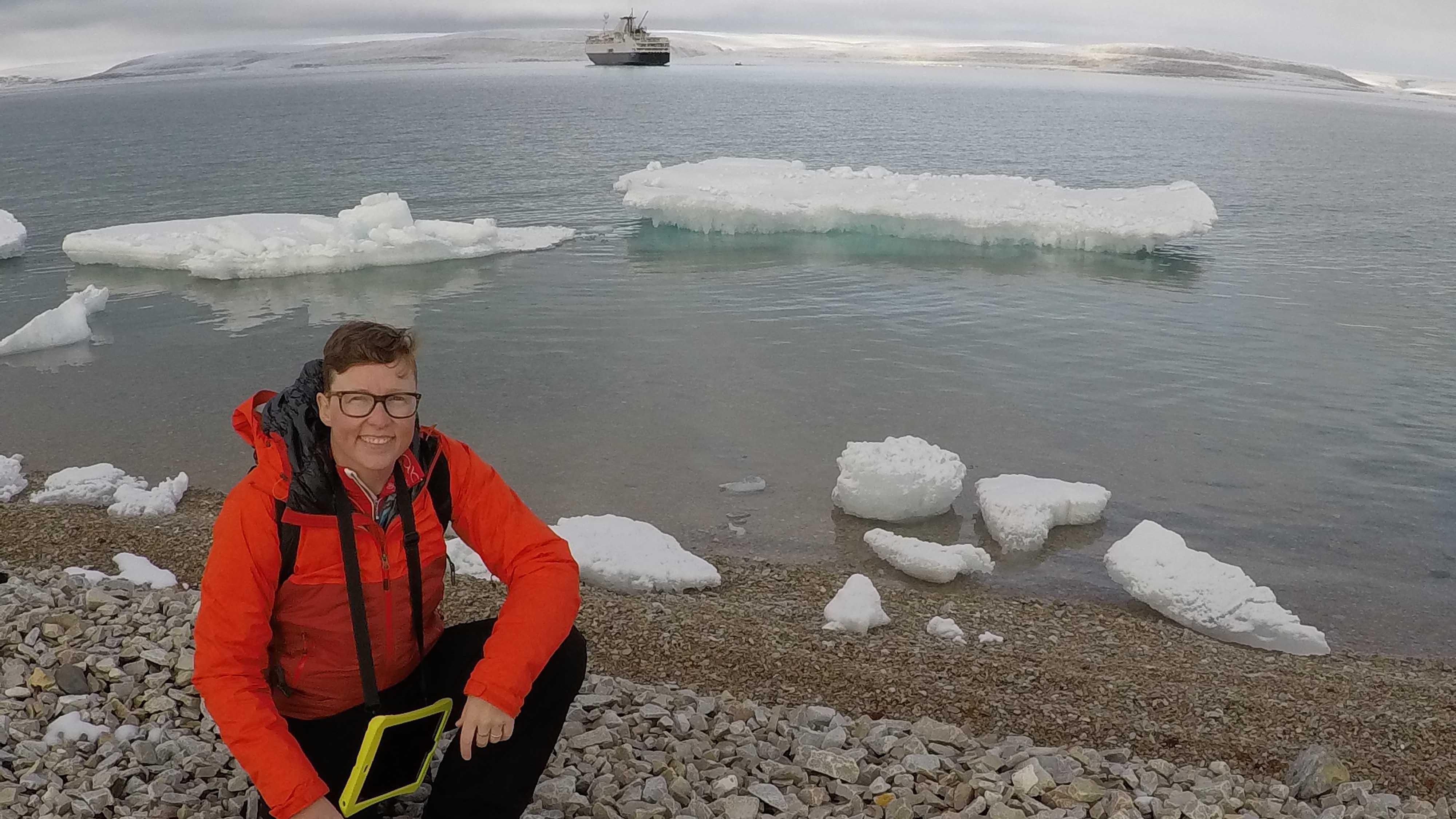 Jackie Dawson près de l'eau avec un navire à l'arrière-plan