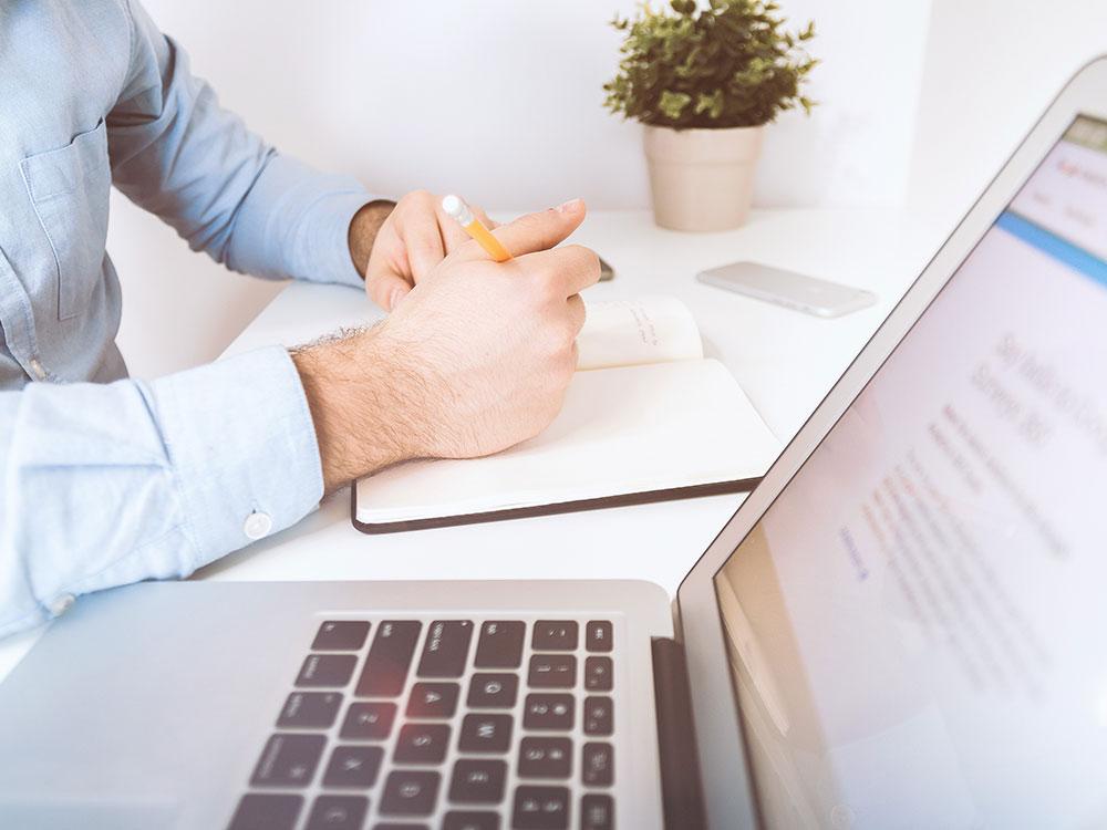 Un homme qui écrit sur un calepin près d'un ordinateur portatif
