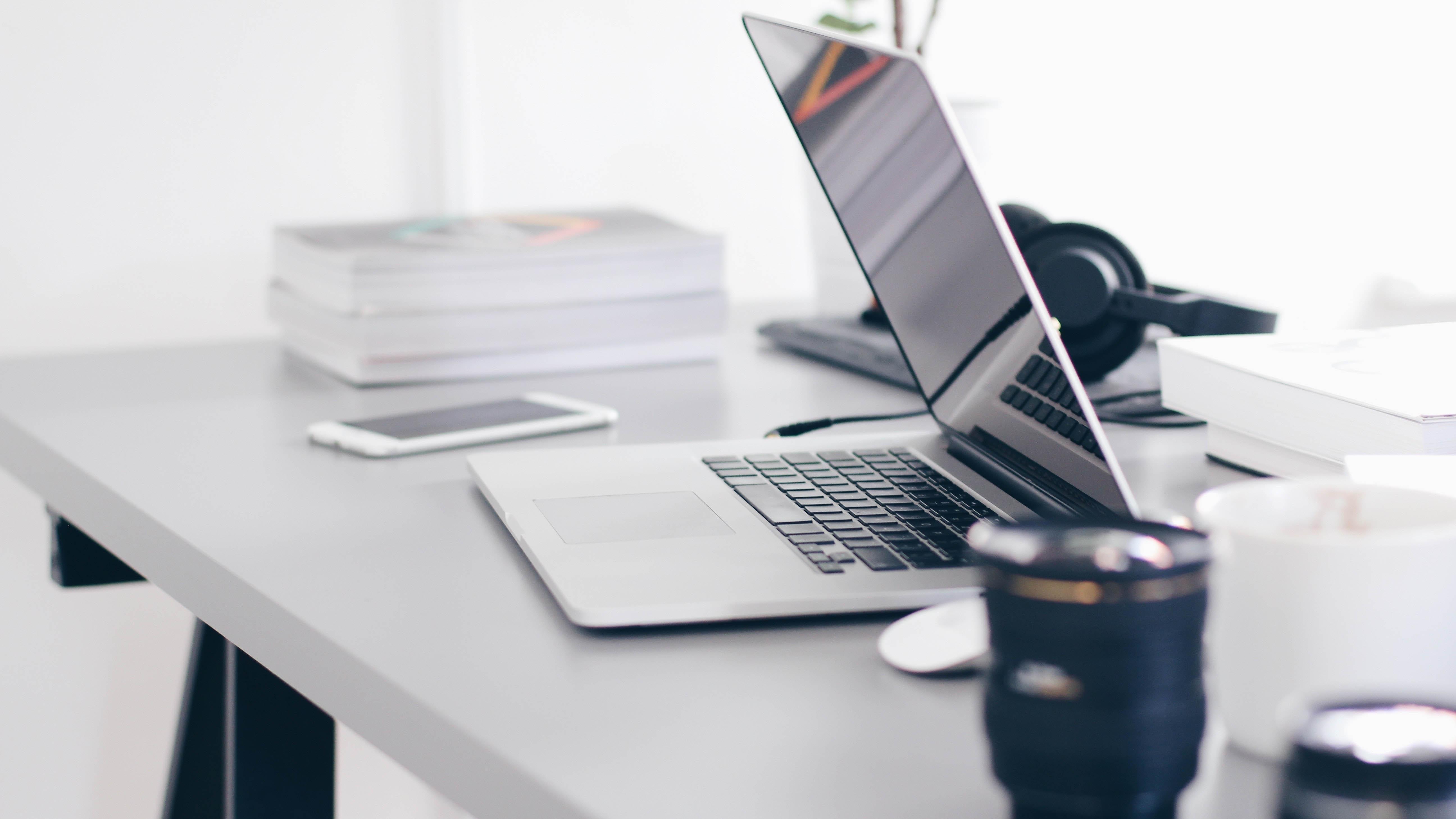 Un ordinateur portable, des livres, des écouteurs, une souris et une tasse de café sont placés sur une table.
