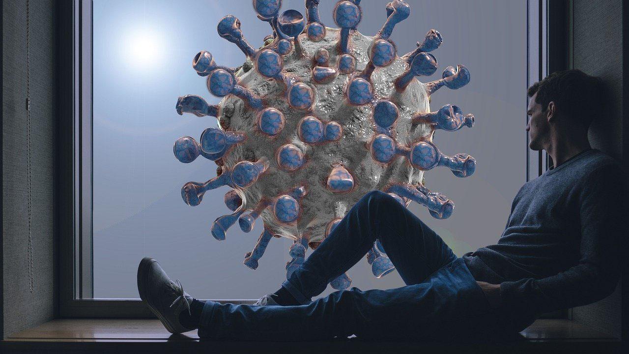 Un homme regarde par la fenêtre et voit un coronavirus