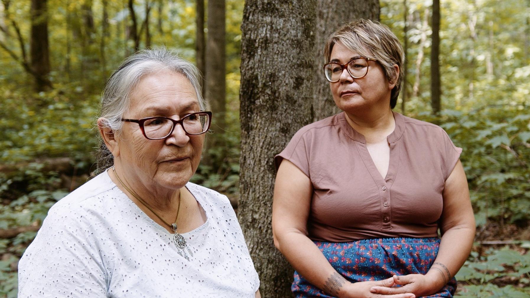 Mariette Niquay et Eva Ottawa sont assises sur une bûche dans le bois.