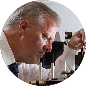 Professeur observe microscope